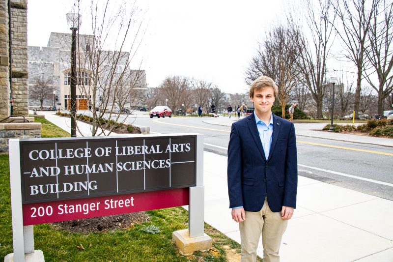 Jonathan Falls stands next to the College of Liberal Arts and Human Sciences building sign.